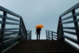 Person mit Regenschirm auf Treppe
