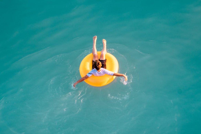 Mann in gelbem Gummiring im Wasser